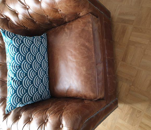 Coussin bleu et blanc sur fauteuil chesterfield