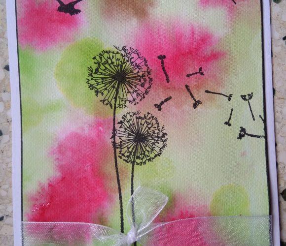 Carte sur fond rose et verte avec fleurs aux vents et oiseaux